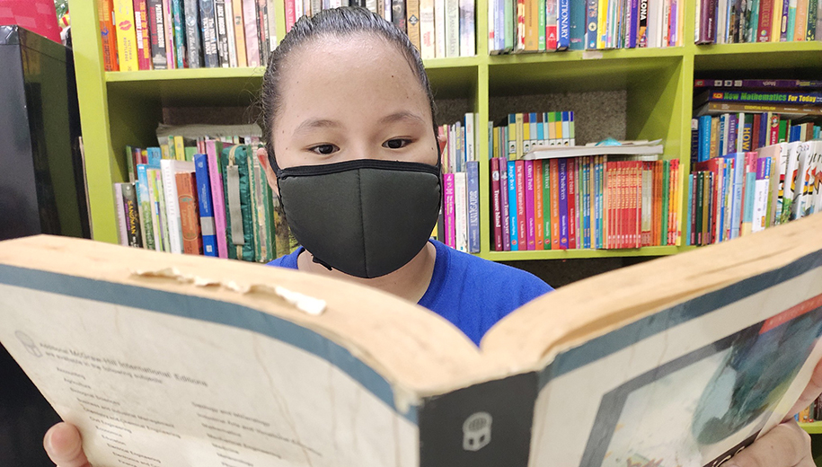 young girl wearing a mask reading - main