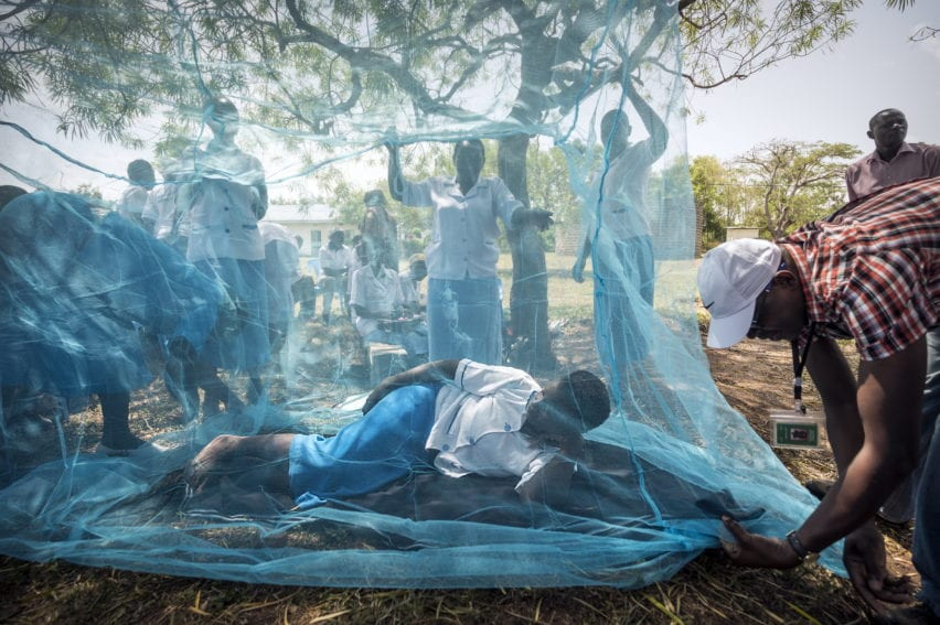 Community health workers demonstrate the use of mosquito nets
