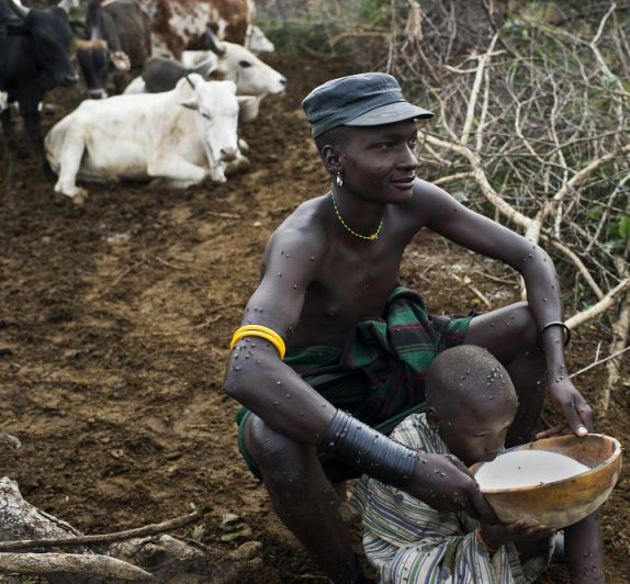 Karamojong pastoralist helps his son to drink milk