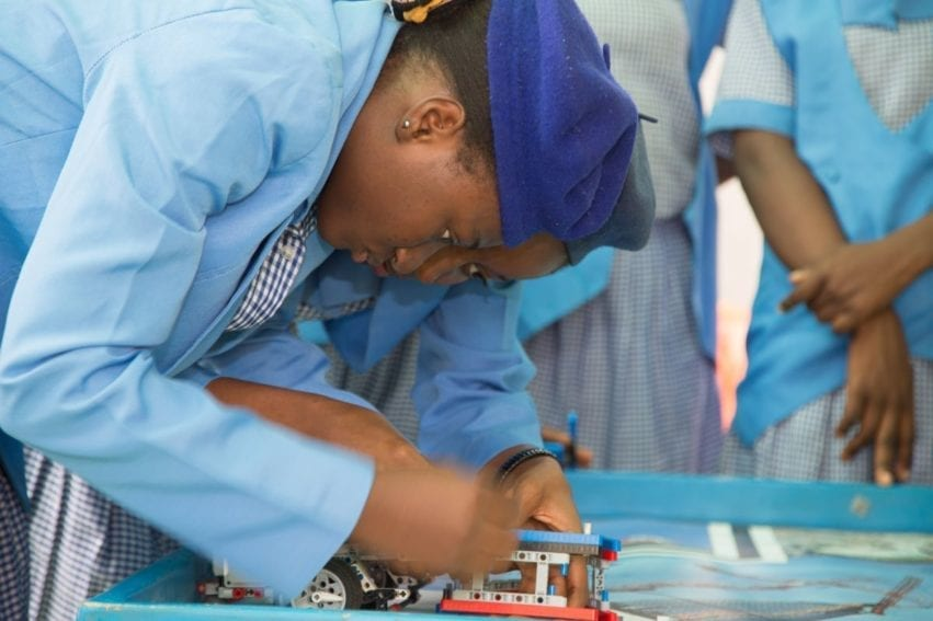 Sixteen-year-old Lawal Alaifan Karimah makes sure the robot is programmed correctly so that it moves across the board picking up garbage and dropping it off in the correct places. She says that a girl can do whatever a boy can