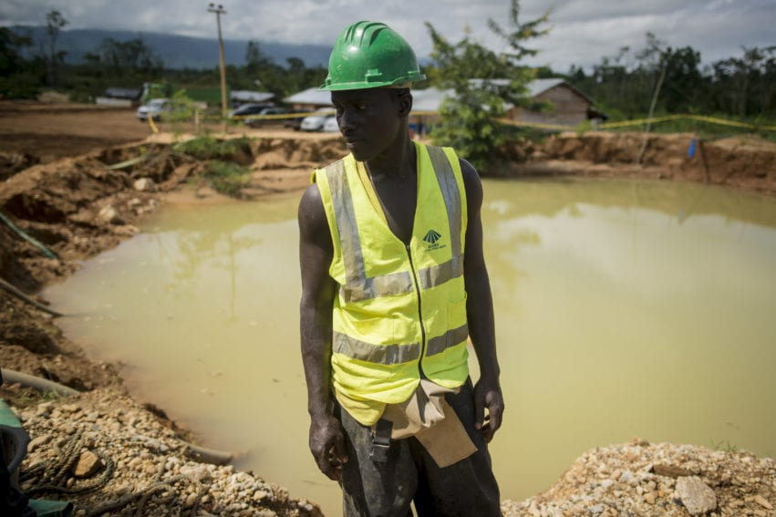 A miner overseeing the gold washing process at Babasala mining site in Kyebi stands next to a pond of water formed after gold prospecting.