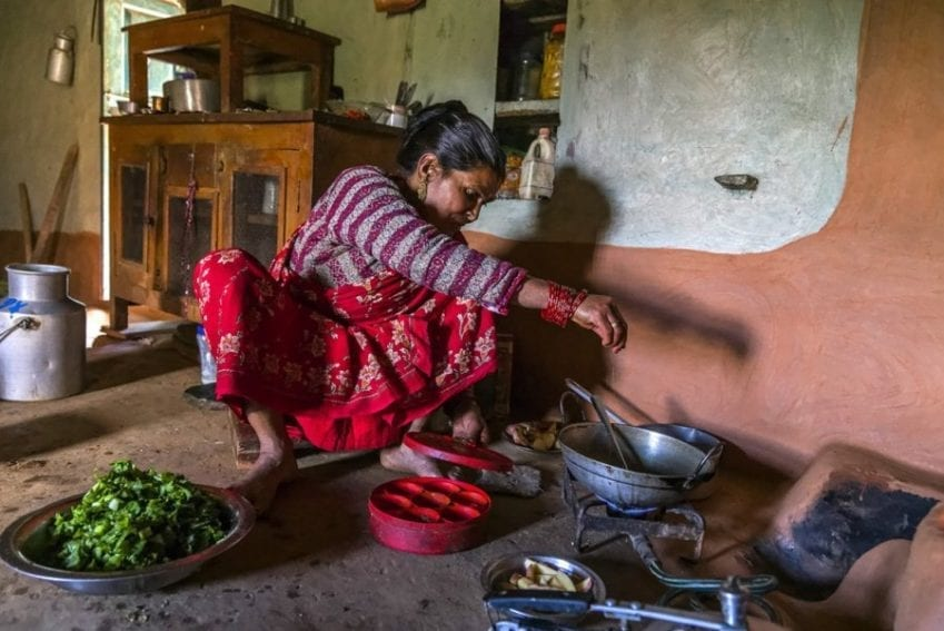 Cooking using gas from a biogas system. Human urine and faeces are mixed with water and collected in an underground pit, where they produce methane that is carried through a narrow pipe into this gas stove