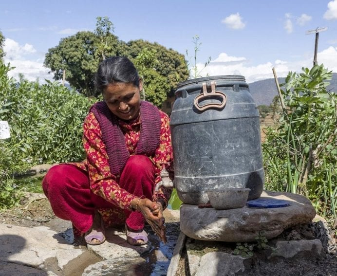 A woman washes her hands in recycled kitchen water after working in her field. A pipe connects the drainage pipe of the sink to a container, so water can be used again for tasks such as cleaning