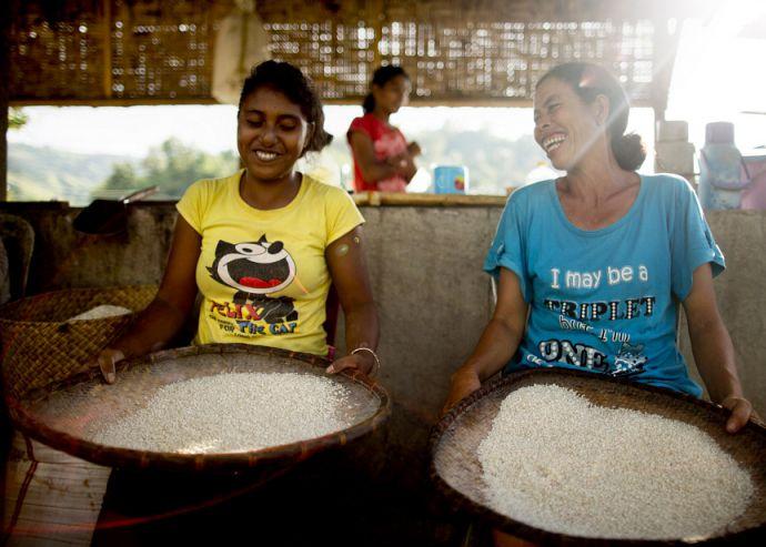 Two women prepare rice