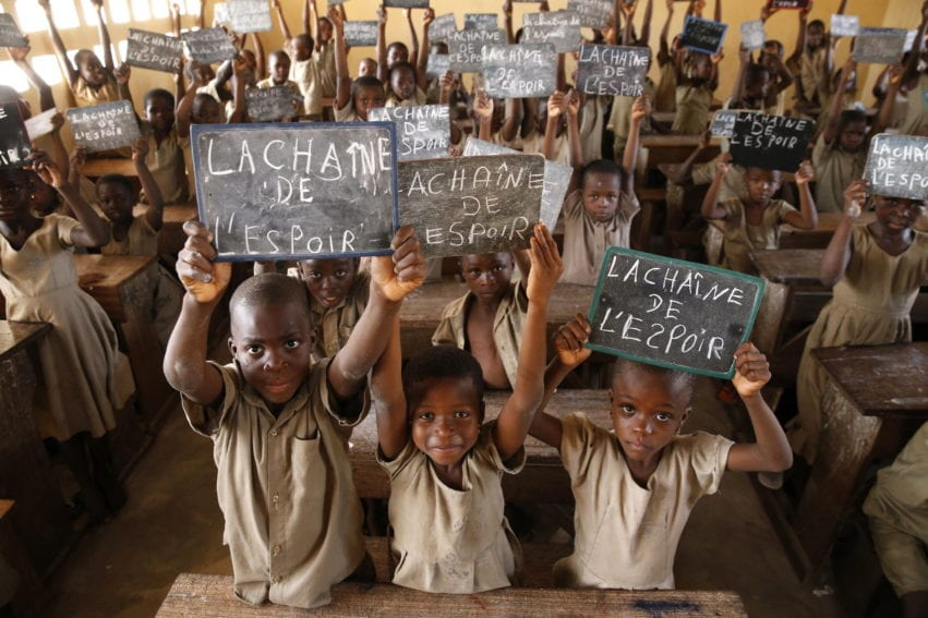 A group of children hold up chalk boards