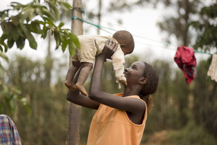 A mother plays with her young son in the Kenyan village of Mwea
