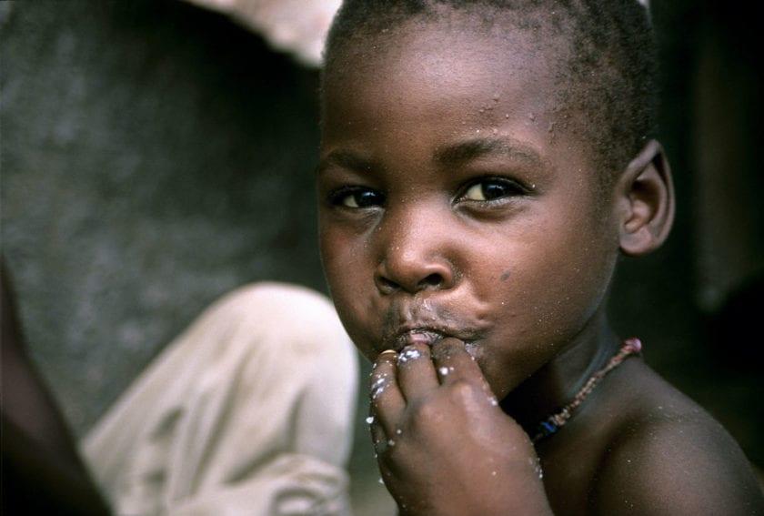 A small boy eating maize porridge
