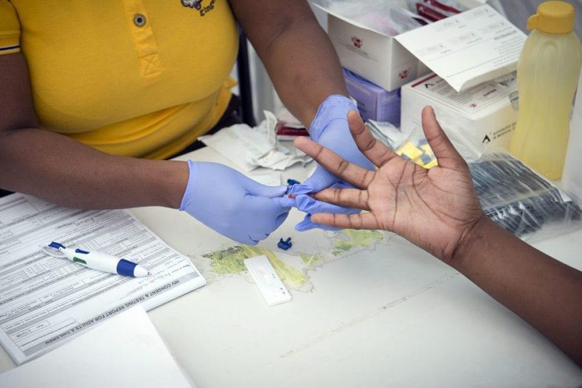 A woman has a blood prick sample taken for an HIV Test