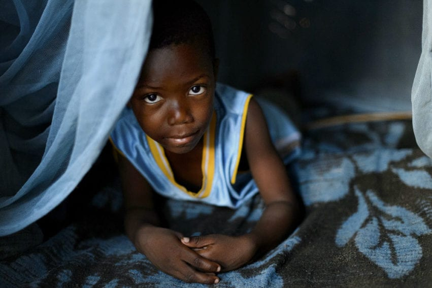 Boy peeks out from under his long-lasting insecticide-treated net