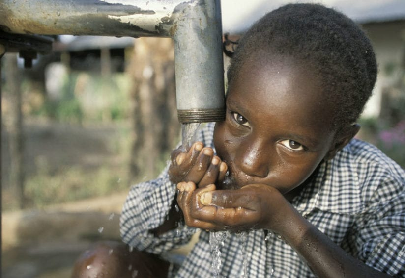 Little girl drinking clean water from a communal pump