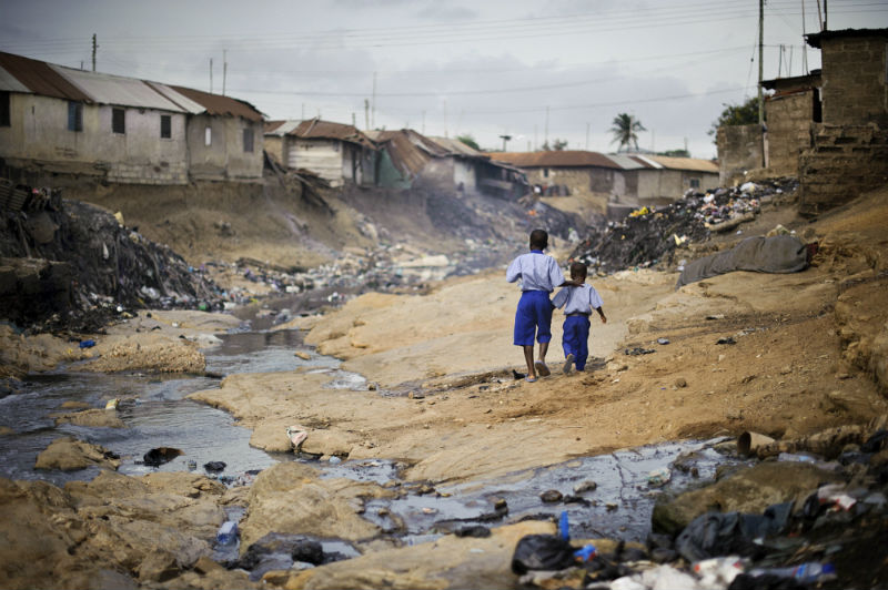 Two children make their way along the polluted gully