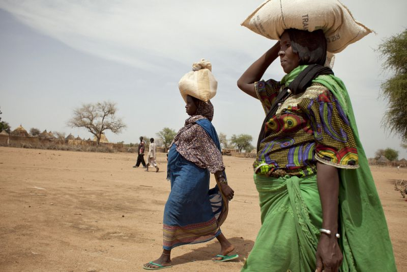 women carrying small sacks of food