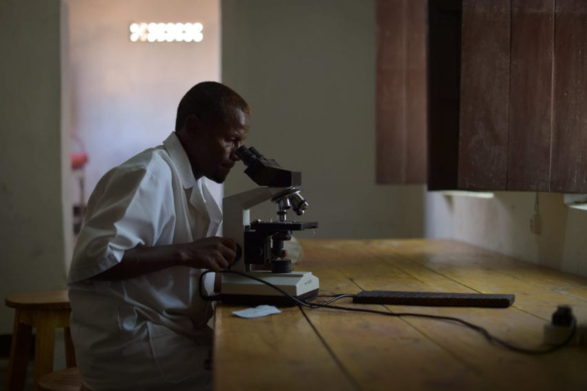 A lab technician checks a blood sample for malaria