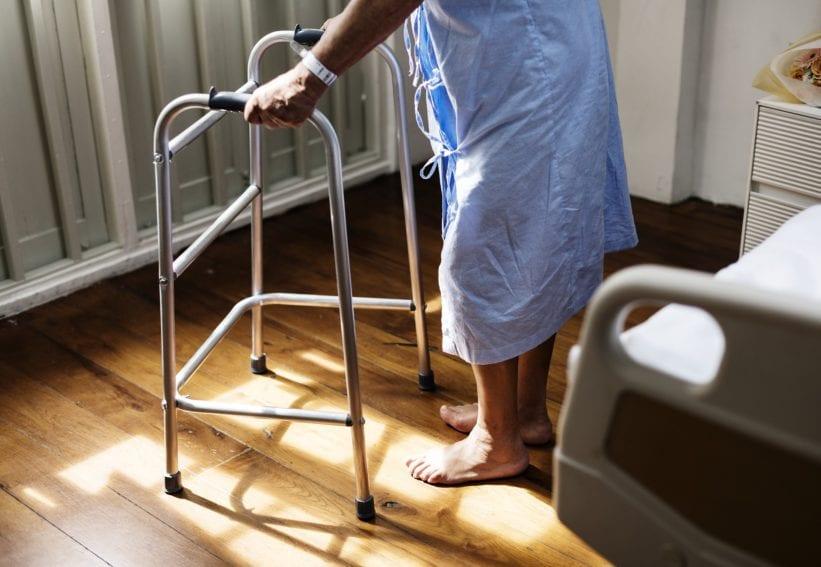 A sick man tries to walk using walking aid