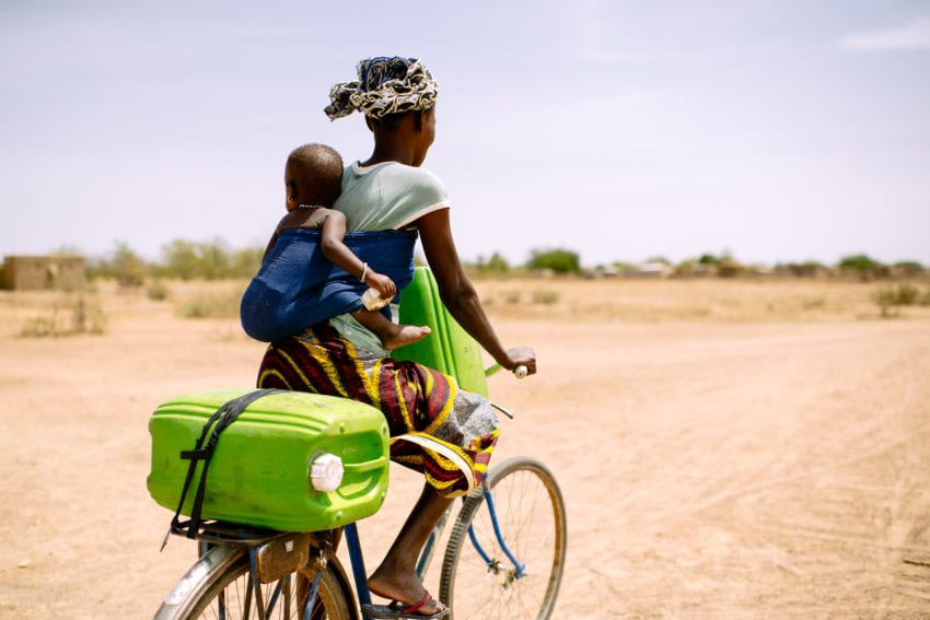 24 years old, rides her bicycle with her baby to collect water for her family