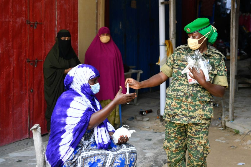 An AMISOM officer distributes face masks to businesswomen